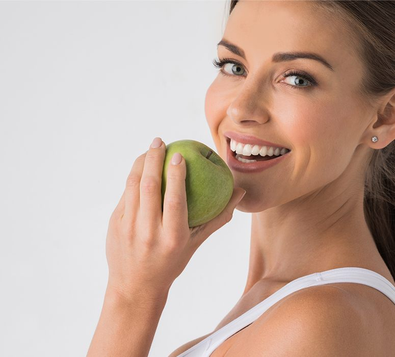 Woman with dentla implant replacement teeth eating a green apple