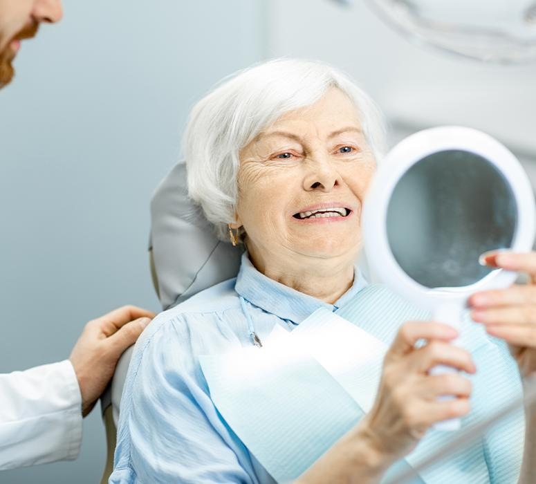 Woman in dental chair after receiving dentures